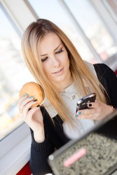 Caucasian attractive woman working using mobile smart phone and laptop eating burger in restaurant background. Text messaging, online banking, playing game, watching video or e commerce shopping