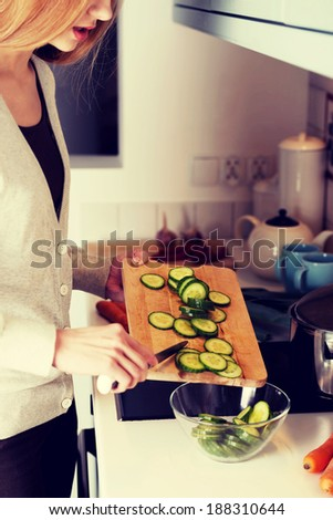 Caucasian attractive young woman is cutting cucumber on kitchen board.