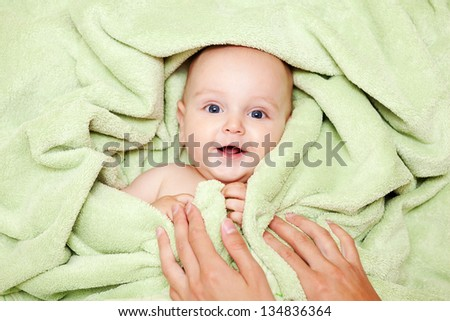 Caucasian baby boy covered with green towel joyfully smiles at camera with mother's hands on him