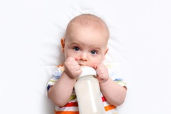 Caucasian baby boy with baby milk bottle on white blanket. Close up. Baby feeding and artificial nutrition concept. Cute baby in striped jumpsuit. Top view.