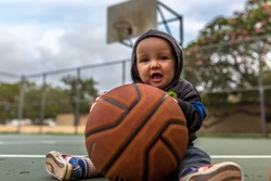 Caucasian Baby on Basketball Court in Athletic Clothes.