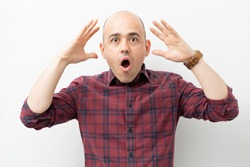 Caucasian bald man with mouth open looking shocked and surprised with his mind blown