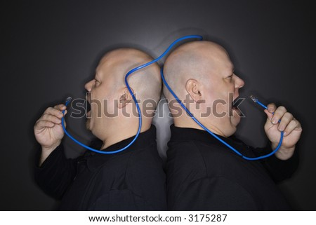 Caucasian bald mid adult identical twin men standing back to back yelling into ethernet cable.