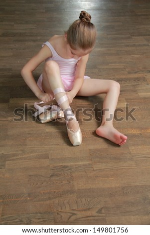 Caucasian ballerina warming up in pointe in the ballet hall on the wooden dance floor