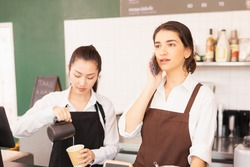 Caucasian barista woman confirms online orders with customer via mobile, Asian barista woman fills white milk into takeaway coffee cup at cafe bar. Barista work at coffee bar and food service business