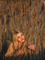 Caucasian beautiful blonde woman in sand or brown sweater in reeds in winter.  Enlightenment, zen, enlightenment, harmony, spiritual, awakening, consciousness, ecology, love, balance, serenity concept
