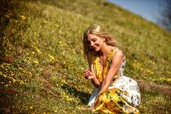 Caucasian beautiful blonde woman looking at a flower. Buddha, zen, healthy life, awakening, meditation, harmony, balance, relax,  mindfulness, enlightenment, consciousness, spirituality concept.