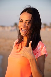 Caucasian beautiful girl smiling happy on beach vacation enjoying warm sunshine. Mixed race Asian Caucasian pretty model outside with sun in background on tropical beach.