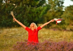Caucasian beautiful happy blonde woman in a red dress puts hands in the air holding hat and flowers on the background of the fields. Mindful, harmony,  spirituality, awakening, consciousness concept.