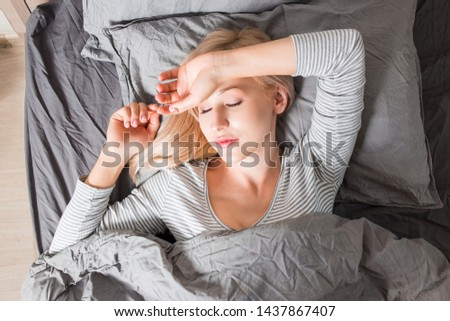 Caucasian beautiful restful blonde woman lying in bed and sleeping peacefully in morning, enjoying comfort and softness of bedclothes, wearing striped sleepwear. Good rest and bed time. Top view.