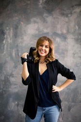 Caucasian beautiful woman photographer is taking images with photo camera. Portrait of a smiling woman standing with photo camera at copy space isolated over gray background