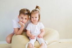 Caucasian big brother and little sister playing at home, children relationship, teenage boy with her toddler playful sister.  International day of brother and sister.