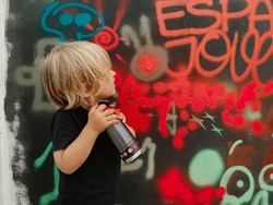 Caucasian blonde toddler looking at the graffiti he has just painted on the wall with a red spray
