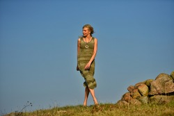 Caucasian blonde woman in green dress standing  at the stone pagan altar. Lifestyle, harmony, balance, contrast, zen, mindfulness, healthy, ecology, spirituality, awakening, consciousness concept.