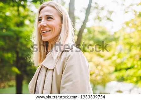 Caucasian blonde woman smiling happily on sunny summer or spring day outside walking in park. ストックフォト ©
