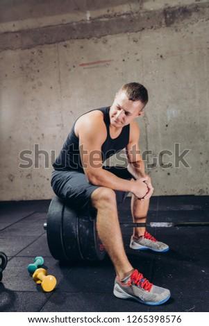 Caucasian bodybuilder resting after training. full length photo. break time. free time