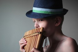 Caucasian boy in hat playing pan pipes