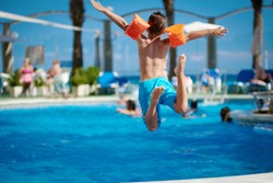 Caucasian boy jumping into the pool.
