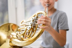 Caucasian boy learns to play the horns, a child plays a wind musical instrument. Light window, real interior.