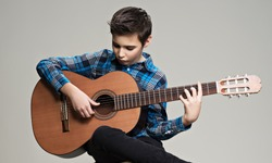 Caucasian  boy playing on acoustic guitar. Teenager boy with classic wooden guitar