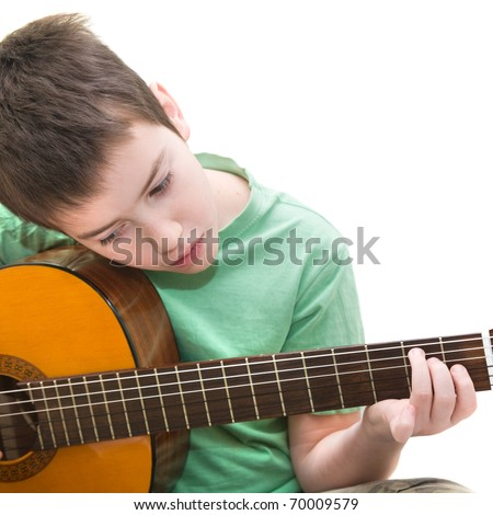 caucasian boy practicing; playing acoustic guitar; isolated on white background;