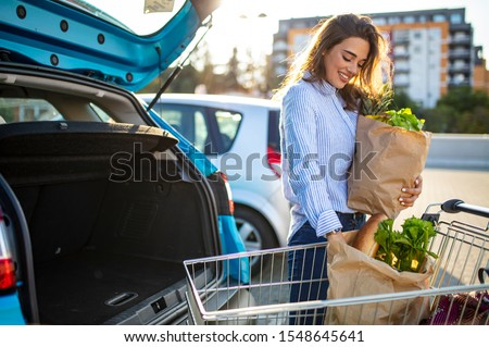 Caucasian brunette going holding paper bags with food products. Young woman putting package with groceries and vegetables into car trunk. Attractive caucasian female shopping in mall or grocery store