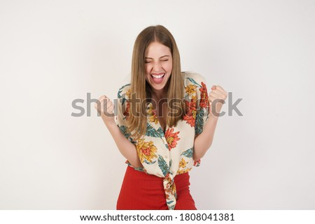Caucasian brunette woman rejoicing her success and victory clenching her fists with joy. Lucky woman with hair bun being happy to achieve her aim and goals. Positive emotions, feelings. Photo stock ©