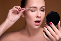 Caucasian brunette woman tweeze her eyebrowns. Close up portarait. Skin care  concept