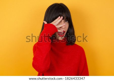Caucasian brunette woman wearing red casual sweater isolated over yellow background peeking in shock covering face and eyes with hand, looking through fingers with embarrassed expression. stock photo