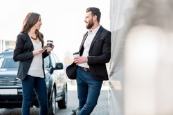 Caucasian business couple standing together on the street near the car during the coffee break
