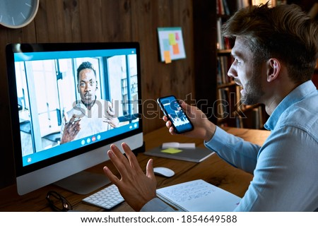 Caucasian business man financial advisor, stock trader, broker consulting african client investor about investment on video conference call virtual remote meeting chat using pc computer and phone app.