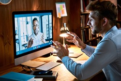 Caucasian business man talking with african male partner coach on video conference call discussing social distance work at virtual remote meeting videoconference chat using pc computer at home office.