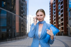 caucasian business woman in a blue jacket and dress talking on the phone with a folder of papers in her hand against the background of an office building
