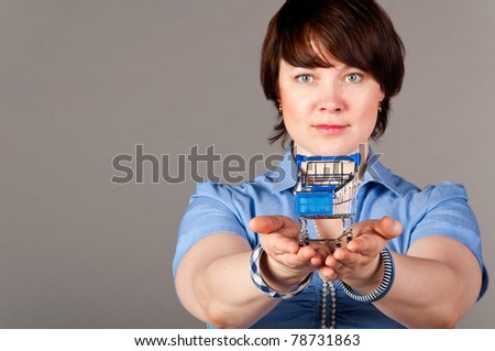 caucasian business woman is holding shopping cart in hands, focus on cart.