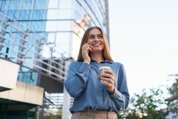 Caucasian business woman speaking by phone holding coffee to go. A successful European woman, talking on the phone, standing on modern office building background