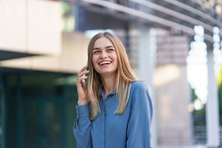 Caucasian business woman speaking by phone. Waist up portrait of a successful European woman, talking on the phone, standing on glass background, modern office building.