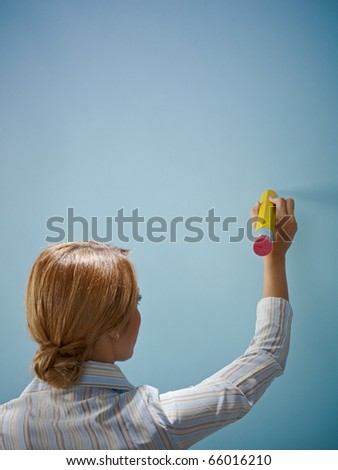 caucasian business woman writing a message on blue wall. Vertical shape, rear view, copy space