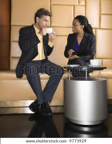 Caucasian businessman and African American woman drinking coffee.