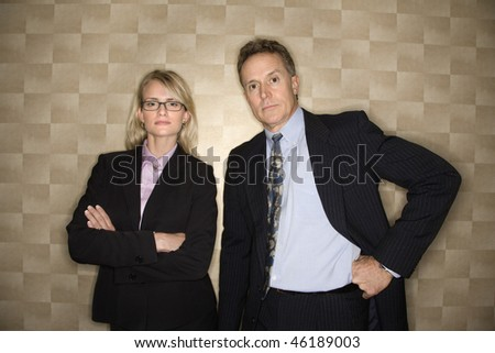 Caucasian businessman and business woman confidently stand shoulder to shoulder as they look towards the camera. Horizontal shot.