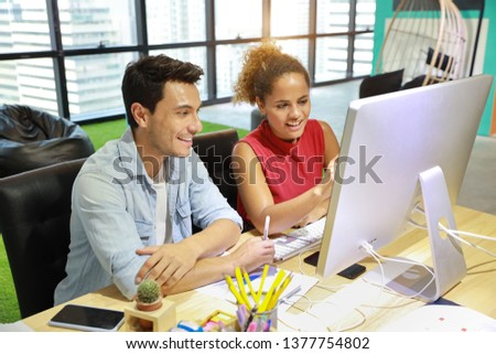 caucasian businessman and businesswoman in smart casual wear working on computer on wood desk in creative office with happy face