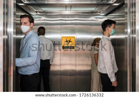 caucasian businessman and people standing apart from each in corner of elevator for social distancing to avoid coronavirus covid-19 spreading with coronavirus alert sign in elevator, selective focus