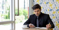 Caucasian businessman in black suit taking a note while reading text message on mobile phone during lunch break. Atmosphere in a modern cafe.