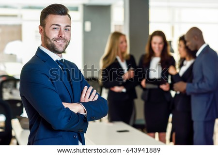 Caucasian businessman leader looking at camera in modern office with multi-ethnic businesspeople working at the background. Teamwork concept. Young man with beard wearing blue suit. #643941889
