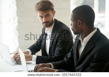 Caucasian businessman looking at african business rival with hate dislike envy, diverse competitors in suits working in office on laptops, multiracial colleagues enemies showing rivalry at work