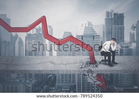 Caucasian businessman looks stressed while sitting on the chair near declining arrow