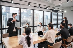 Caucasian businessman presentation of business plan on laptop at conference table, Group of business people wearing face mask meeting in modern office while pandemic of Coronavirus, Covid 19