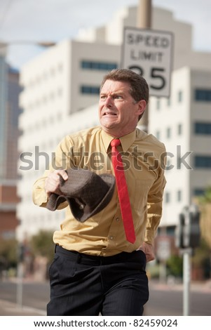 Caucasian businessman runs on the streets to make it to meeting on time