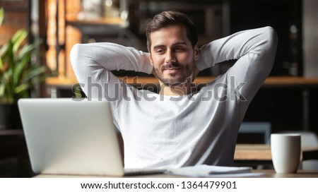 Caucasian businessman sitting at table in cafe modern cozy office looking at laptop screen feels satisfied proud with done work, serene man resting putting hands behind head relaxing no stress concept