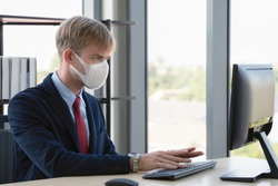 caucasian businessman with medical mask for coronavirus covid-19 protection working in office, new normal business practise of coronavirus covid-19 outbreak control