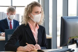 caucasian businesspeople with medical mask for coronavirus covid-19 protection working in office, new normal business practise of coronavirus covid-19 outbreak control